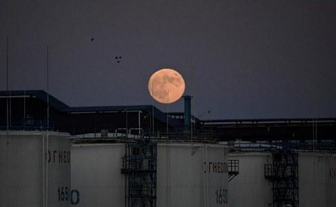 Oil edges higher on weaker dollar, but demand threats cap gains