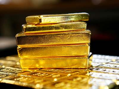Gold eases as dollar gains on strong US data, but eyes weekly gain