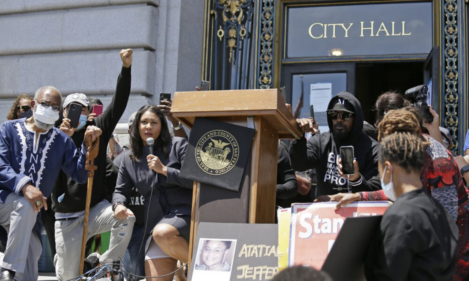 "Jamie Foxx, right of podium, and Mayor London Breed, left of podium, take part in a ""kneel-in"" to protest police racism on the steps of City Hall on Monday, June 1, 2020, in San Francisco. Hundreds watched the noontime demonstration. Photo by AP"