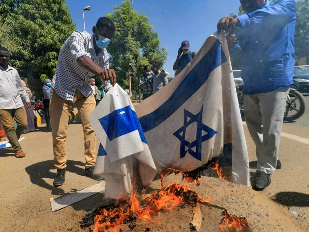 Sudan protesters burn Israeli flag in rally against normalisation deal