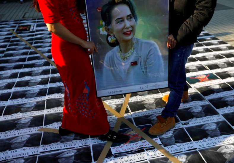 Myanmar protesters residing in Japan stand on pictures of Myanmar's army chief Min Aung Hlaing as they rally against the country's military after it seized power from a democratically elected civilian government and arrested its leader Aung San Suu Kyi, shown in the portrait, at United Nations University in Tokyo, Japan February 1, 2021. Source: Reuters.