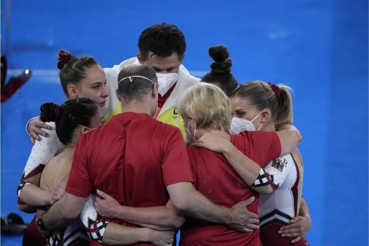 Team Germany huddles together after performing in the women's artistic gymnastic qualifications